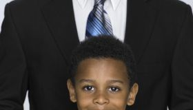 Boy (3-5) standing in front of father, portrait