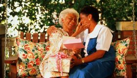 Mature woman giving elderly mother gift and card on porch swing
