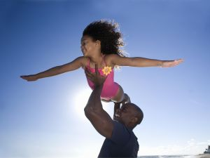 Father carrying daughter (6-7) on beach