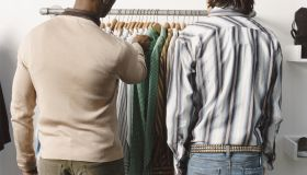 Rear View of Two Men Looking at Shirts on a Clothes Rail