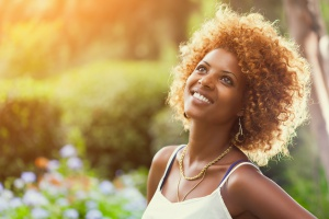 Smiling African woman in sunshine Outdoors profile portrait