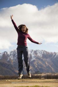 Young woman jumping on idyllic landscape