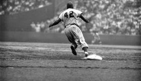 Dodger Jackie Robinson rounds first during a game against the Giants.