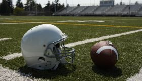 Football and football helmet on football field