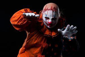 Creepy Halloween Clown in Bloody Mask, Portrait on Black