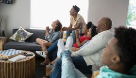 African American family watching TV in living room
