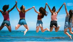 Female friends jumping against sea and sky