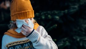 Little boy having a cold, blowing his nose