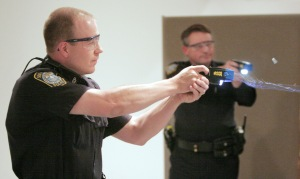 Christopher Todd, an officer with the South Portland police department, fires his taser gun during a