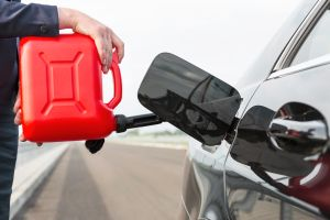 Businesswoman fueling car with petrol can