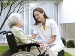 Nurse talking with elderly woman at garden