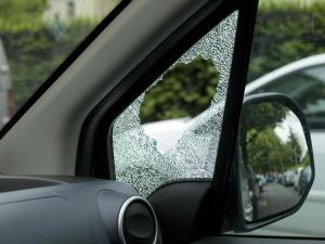 Broken side window of burglarized car, street view