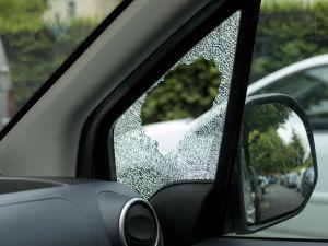 Broken side window of burglarized car, street view