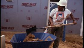 Habitat for Humanity Worker Shovels Dirt Into Wheelbarrow