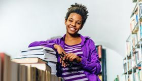Pensive black girl in library posing with books