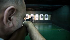 Man aiming with a carbine in an indoor shooting range