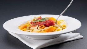 Dish of rigatoni pasta topped with tomato concasse