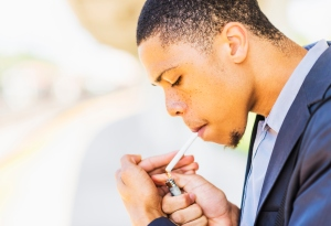 Black businessman lighting cigarette outdoors