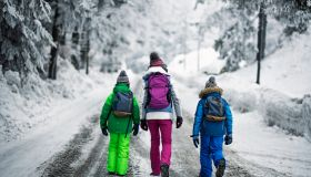 Kids with backpacks walking on winter road