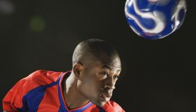 African American man bouncing soccer ball on head