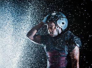 Water splashing on black football player