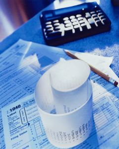 Tax forms, receipt, calculator and pencil, close-up
