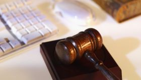 Close-up of computer keyboard and mouse with textbook and gavel beside it
