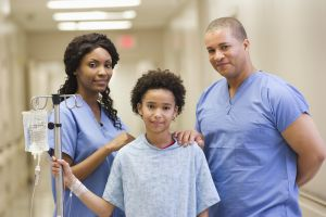 Doctors and patient with IV in hospital corridor