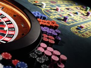 Gambling chips stacked around roulette wheel on gaming table