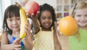 Children holding out fresh fruit