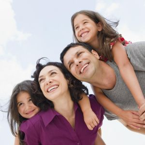 Smiling parents giving daughter's piggyback ride