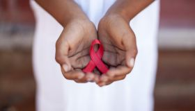 Child's hands holding an HIV awareness ribbon, Cape Town, South Africa
