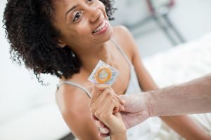 Woman with condom and hand of partner