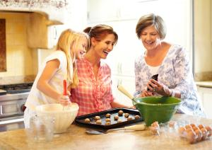 Grandmother showing smart phone to daughter and granddaughter