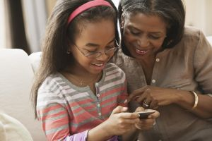 African American grandmother and granddaughter looking at cell phone