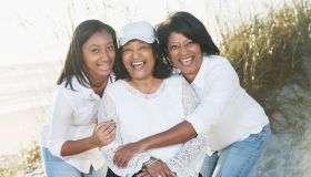 Three generations of black women posing on beach