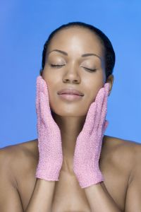 A woman using exfoliation gloves