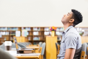 Tired or frustrated African American student studying late in library