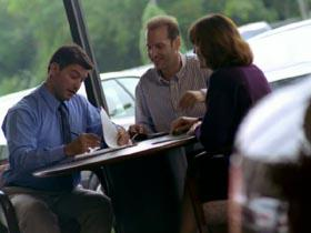 dolly shot zoom in CANTED salesman fillout out forms with couple in car dealership