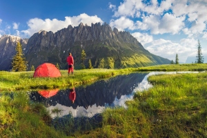 Camping with tent near high altitude lake on the Alps. Reflection of snowcapped mount Hochkönig range and scenic cloud sky