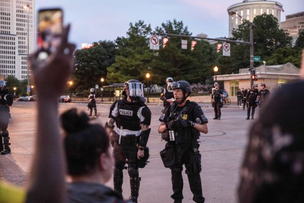 Riot police stand on guard outside the state house during...