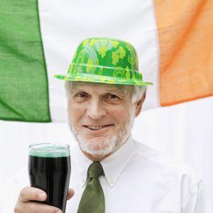 Elderly man dressed as a leprechaun holding a glass of stout