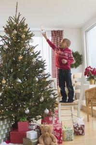 African American boy decorating Christmas tree