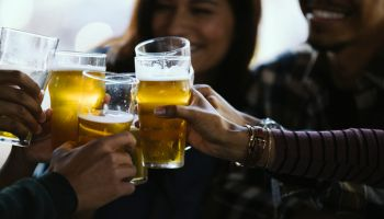Close-up of happy friends toasting beer glasses in pub