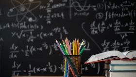 Back to school supplies. Books and blackboard on wooden background,education