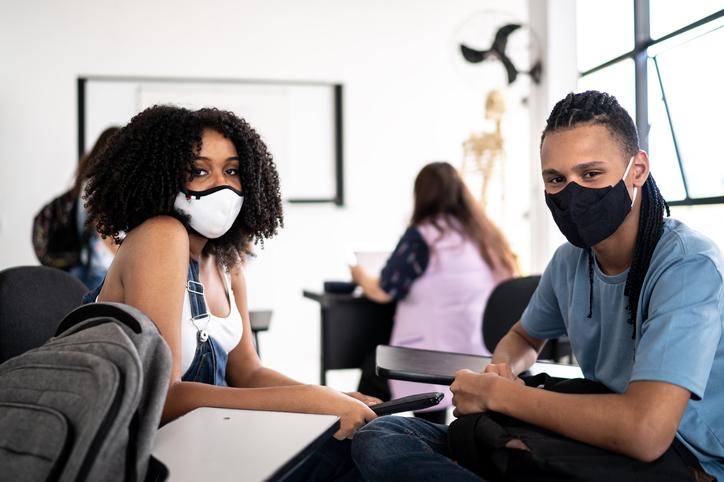 Portrait of friends wearing face mask in class room