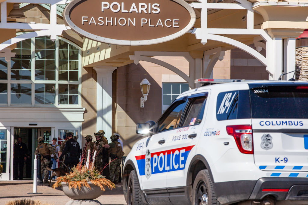 Police officers enter the Polaris Fashion Place. Around 12:...