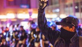 Protester raises his fist on High St. with a line of Police...