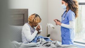 As nurse stands by bed, the senior woman takes pills