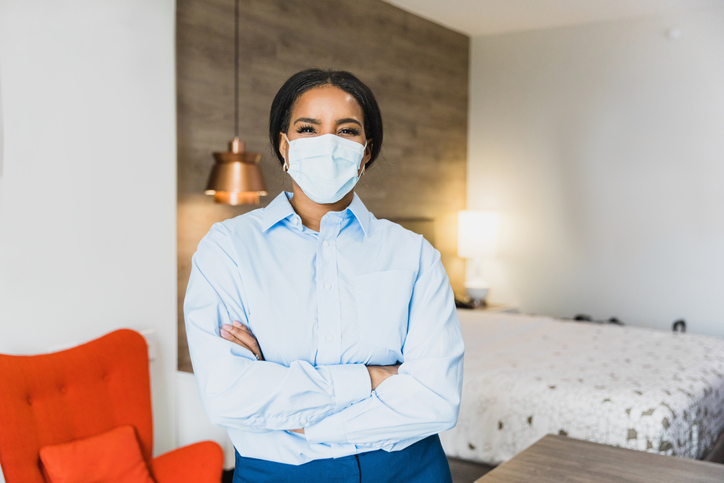 Confident housekeeping manager in hotel room